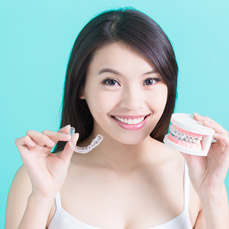 Woman holding model smile with braces and Invisalign tray