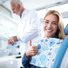 A woman giving a thumbs-up at a dental office.