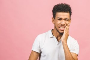 person holding their mouth in pain