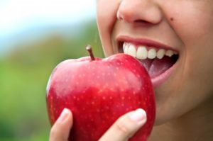 close up of person eating a red apple